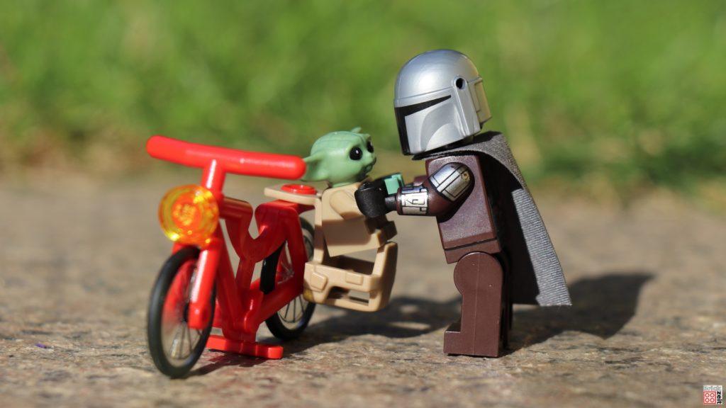 Din Djarin hilft Grogu in seinen Fahrradsitz   ©Brickzeit